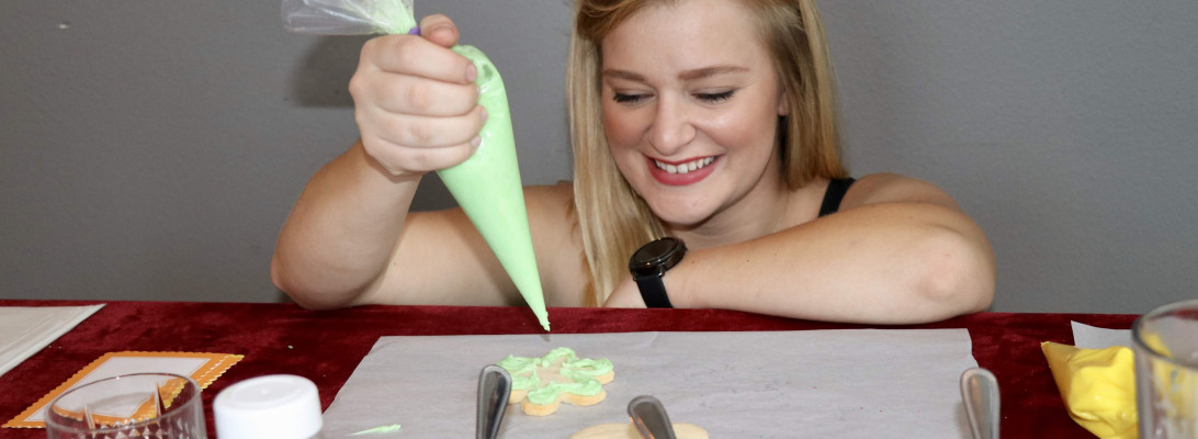 Woman frosting a cookie